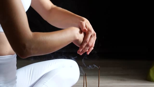 Meditating female sit on bed and relax smoking insence yoga sticks