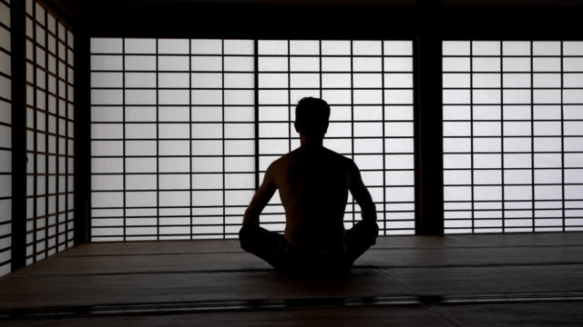 DS Meditating in tatami house Dolly shot of a silhouette of a man meditating in traditional Japanese tatami house. Also available in 4K resolution cross legged stock videos & royalty-free footage