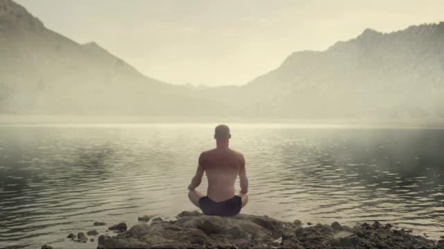 meditating man healing cosmic energy - spirituality stock videos & royalty-free footage