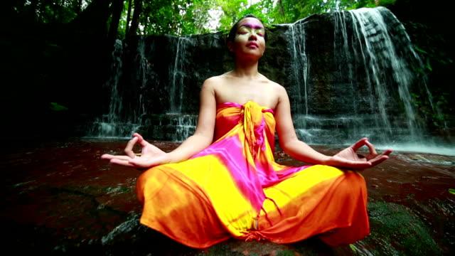 meditating with facial painting in borneo rainforest waterfall - sarong bildbanksvideor och videomaterial från bakom kulisserna