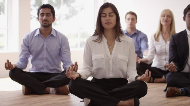 Meditation in the Workplace Coworkers practice meditation on the wood floor as a form of relaxation and de-stressing in the workplace. yoga stock videos & royalty-free footage