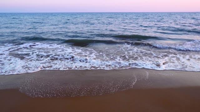 Plage de sable méditerranéenne avec des vagues se brisant sur le rivage - Vidéo