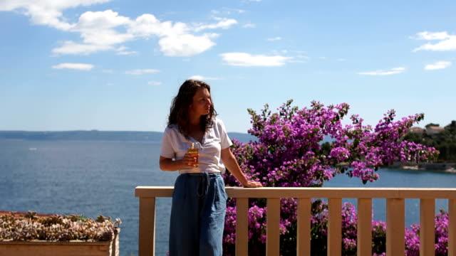 mediterrane meereslandschaft mit mädchen, das auf einen meereshorizont aus schönem holz mit blumen terrasse mit meerblick schaut - reisebüro stock-videos und b-roll-filmmaterial