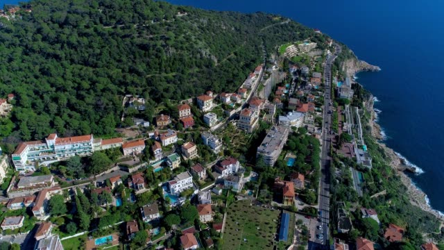 Mediterranean village near Nice in the green hills in sunshine light. rooftops and narrow streets below. mountains and sea in the distance. Summertime in France from aerial 4K drone view