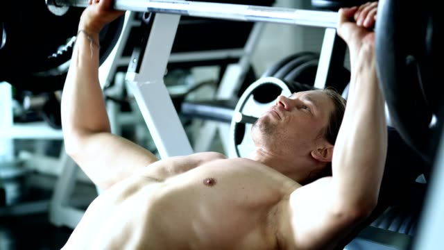 stockvideo's en b-roll-footage met 4k medium close up shot atleet man bodybuilder liggend op gewicht bench en training barbell bench press gewicht training voor kracht en stevige gespierde sport club gym. sterk en gezond concept - bankdruktoestel