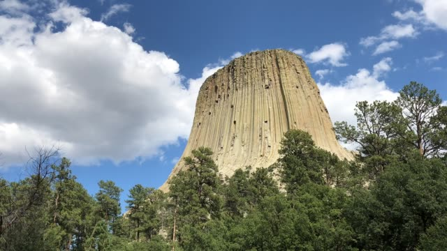 Medium close up time lapse shot of the Devils Tower in Wyoming, with thick white clouds moving over it