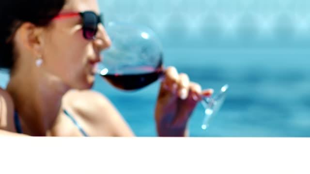 サングラス、池で、赤ワインを飲んで楽しむ日光浴中クローズ アップ肖像画リラックスできる女性 - 赤ワイン点の映像素材/bロール