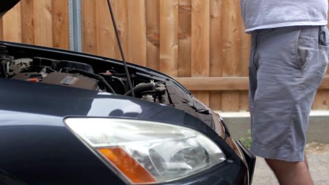 Medium close-up shot of a man closing the hood of a car video
