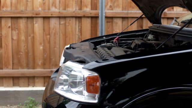 Medium close-up shot of a man closing the hood of a truck video