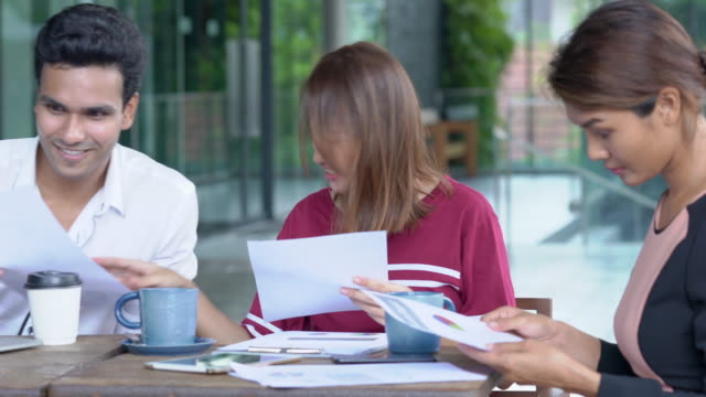 4K Medium dolly shot group of young adult asian businessman and businesswoman freelance discussion about business together at coffee shop outdoor. Teamwork young businessman and businesswoman working together