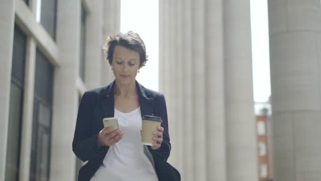 vídeos y material grabado en eventos de stock de carro medio chupito de elegante empresaria edad media con el pelo corto caminando por la calle con celular y taza de café para llevar en sus manos y mirando pensativamente - cabello corto