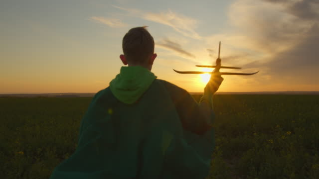 vídeos de stock e filmes b-roll de medium shooting. the boy is running across the field and launching the plane into the sky. sunset. 4k - baby super hero