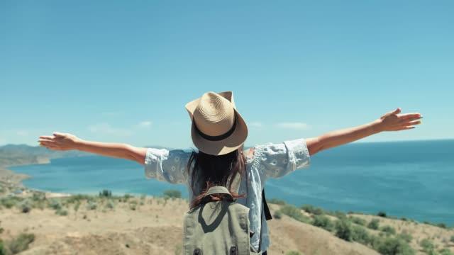 medium sköt aktiva kvinnliga resenären i solglasögon och hatt du beundrar seascape höjande händer - bekymmerslös bildbanksvideor och videomaterial från bakom kulisserna