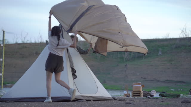 Medium shot. Asian young teenage couple assemble tent blue and yellow together for relaxing in the midst of nature and sunlight. The concept of family lifestyle holiday video
