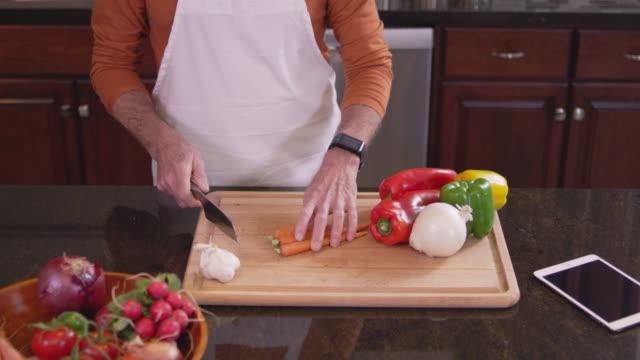 medium skott av en kock hugga upp några morötter på en skärbräda i ett kök - morot bildbanksvideor och videomaterial från bakom kulisserna