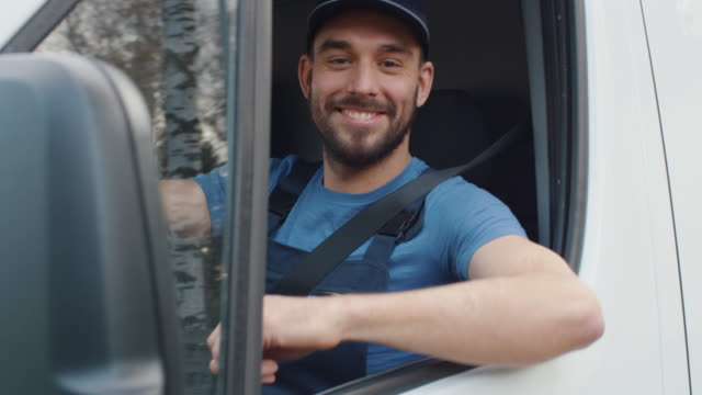 medium shot of a delivery man opening window of his cargo van and smiling at the camera. - тягач с полуприцепом стоковые видео и кадры b-roll