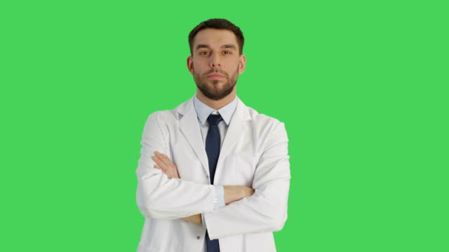 Medium Shot of a Handsome Medical Practitioner Crossing Arms on His Chest and Smiling Warmly. Shot on a Green Screen Background. video