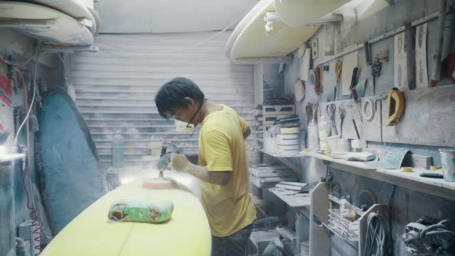 Medium shot of a mature man shaping and polishing a surfboard by hand in his small business surf shop Medium shot of a mature man shaping and polishing a surfboard by hand in his small business surf shop in Okinawa, Japan. small business saturday stock videos & royalty-free footage