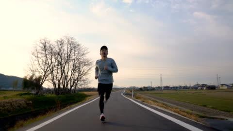 vídeos de stock e filmes b-roll de medium shot of a mid adult man running in the morning - correr