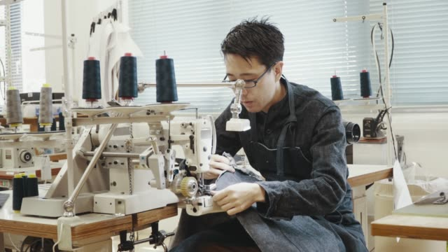 medium shot of a mid adult tailor working at a sewing machine in his design studio - tailor working video stock e b–roll
