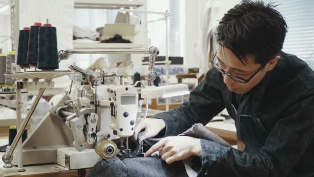 彼のデザインスタジオでミシンで働いているミッドアダルトテーラーのミディアムショット - スタジオ 日本人点の映像素材/bロール