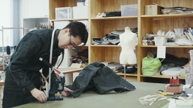 彼のデザインスタジオで働いているミッドアダルトテーラーのミディアムショットは、デニム製品を作成します - スタジオ 日本人点の映像素材/bロール