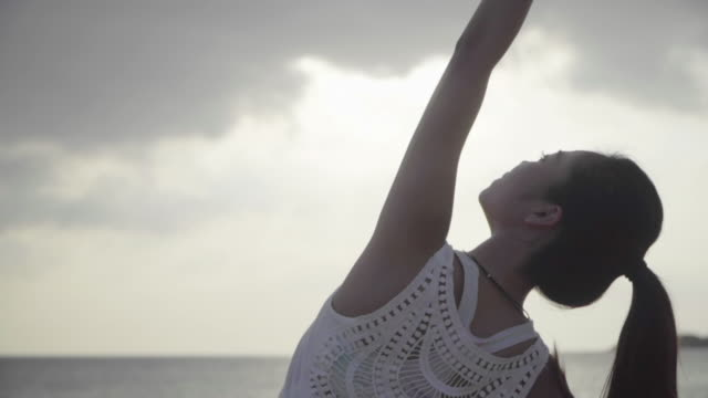 砂浜で屋外でヨガを練習するミレニアル世代の女性のミディアムショット - ヨガ点の映像素材/bロール