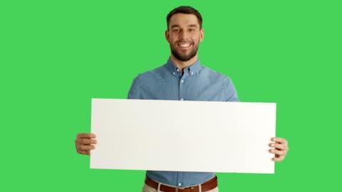 Medium Shot of a Smiling Stylish Man Holding Poster/Placard. Shot on a Green Screen. Medium Shot of a Smiling Stylish Man Holding Poster/Placard. Shot on a Green Screen. Shot on RED Cinema Camera 4K (UHD). holding stock videos & royalty-free footage