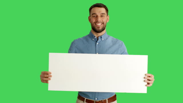 Medium Shot of a Smiling Stylish Man Holding Poster/Placard. Shot on a Green Screen. video