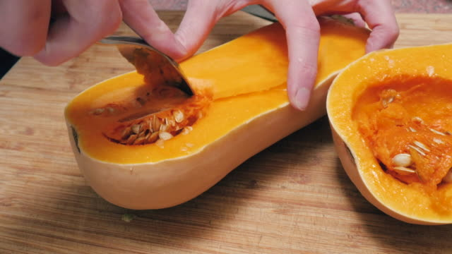 medium shot of a woman scraping seeds from a butternut squash in 4k - zucchini video stock e b–roll