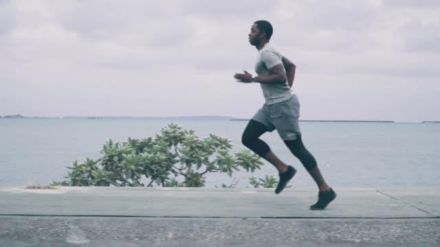 vidéos et rushes de moyen tiré d'un jeune homme jogging le long de la côte en slow motion - vue latérale