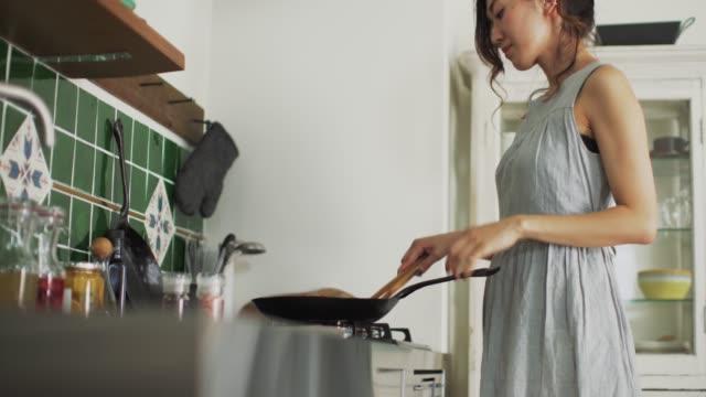 vídeos y material grabado en eventos de stock de tiro medio de una mujer joven cocinando usando una sartén, un hombre hablando con - cocina doméstica