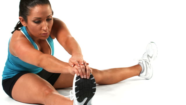 Medium shot of a younger sporty female stretching on the floor Medium shot of a younger sporty female stretching on the floor human joint stock videos & royalty-free footage