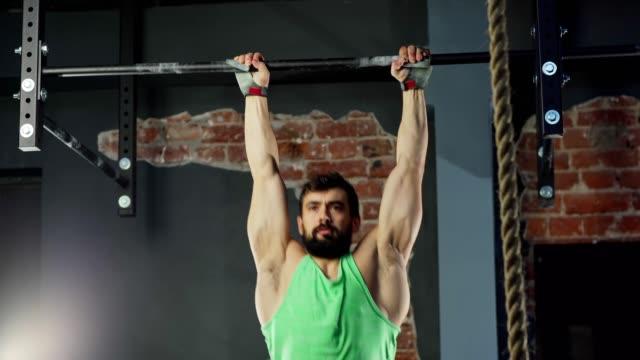 mittlere aufnahme von athletischen bärtigen jungen mann blick auf die kamera, während zehen zu bar bein erhöht üben bauchtraining auf pull-up-bar - turngerät mit holm stock-videos und b-roll-filmmaterial