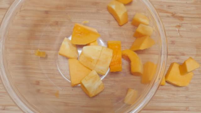 vídeos de stock, filmes e b-roll de dose média de cubos de abóbora, caindo em um vidro de saladeiras em 4k - dieta paleo