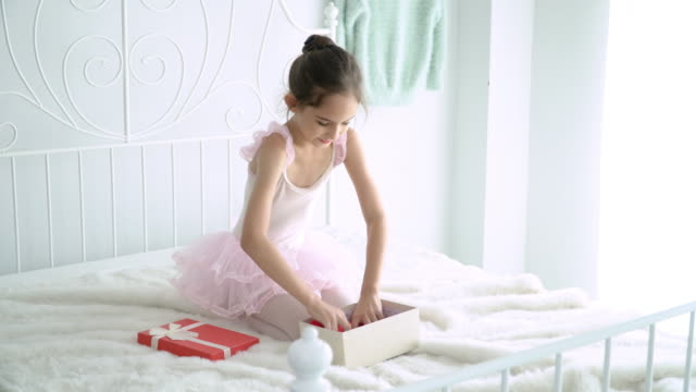 4K Medium shot of happy beautiful little girl in pink ballet tutu and leotard sitting on the bed in bedroom and playing mini red heart. Cute child girl in pink ballet dress playing alone on the bed