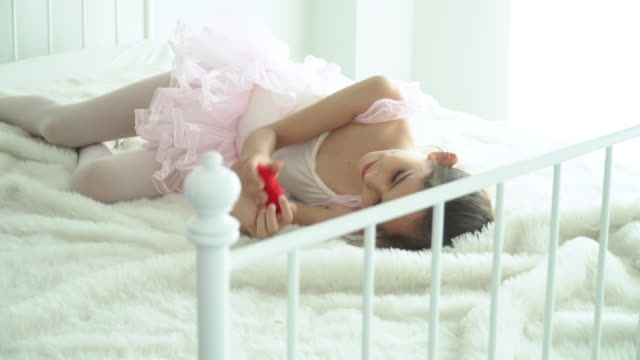 4K Medium shot of happy beautiful little girl in pink ballet tutu and leotard lying down on the bed in bedroom and playing mini red heart. Cute child girl in pink ballet dress playing alone on the bed