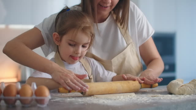 Medium shot of mother and daughter rolling dough in kitchen. Mom teaches daughter to cook dough. Girl learns to cook pastries. Kneading the dough together. Roll out the dough for baking.