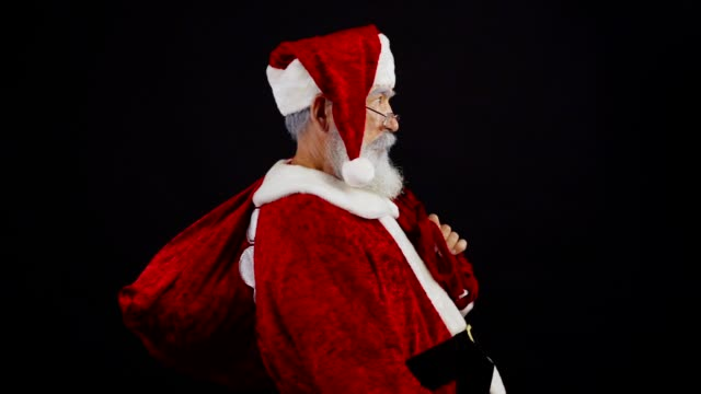 medium shot of santa claus with christmas sack walking into frame in slow motion against black background, showing you shh gesture and tiptoeing away trying to be unnoticed - santa claus tiptoeing video stock e b–roll