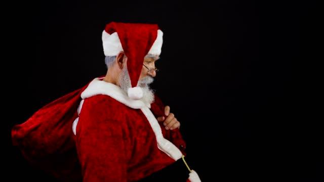 medium skott av jultomten med jul säck gå in i ramen, visar dig shh gest och tiptoeing bort försöker vara obemärkt - på tå bildbanksvideor och videomaterial från bakom kulisserna