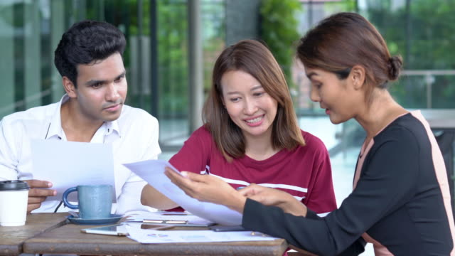 4K Medium shot of teamwork young businessman and businesswoman working together. Group of young adult asian businessman and businesswoman freelance discussion about business together at coffee shop outdoors
