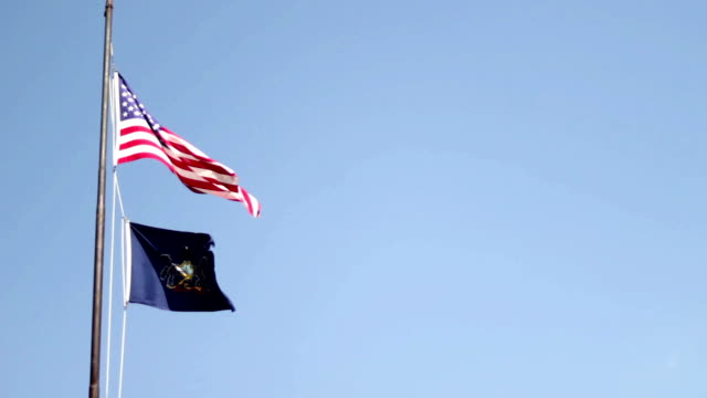 A medium shot of the american flag fluttering with the Pennsylvania Coat of Arms flag video