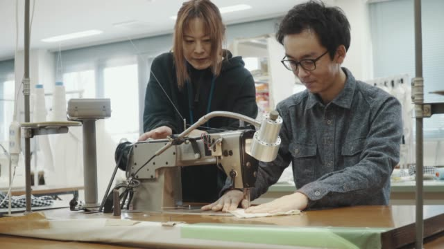 Medium shot of two mid adult design professionals working together in a textile manufacturing studio Medium shot of two mid adult design professionals working together in a textile manufacturing studio in Japan mid adult men stock videos & royalty-free footage
