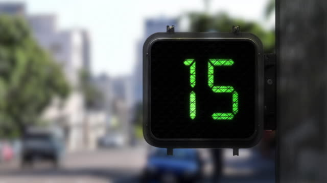 Medium shot of Walk Signal with a Green display as it shows a 15 second countdown with traffic in the background