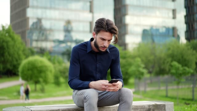 Medium shot of young businessman sitting on bench in small park and typing text messages on cell phone being serious and smiling slightly
