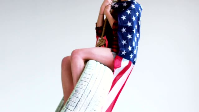 Medium shot of young Caucasian girl with waving American flag riding on a tire swing against white background video