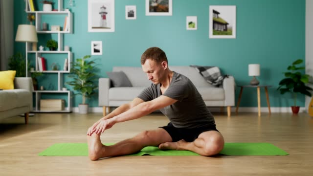 Medium shot of young man doing yoga in the morning in his living room video