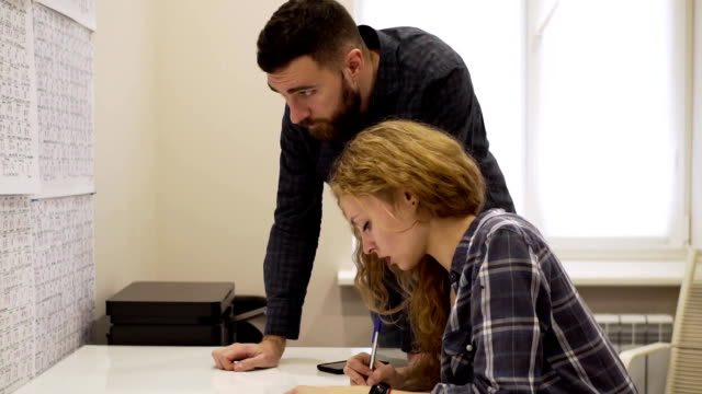Medium shot of young man helps a girl learn Chinese characters in the classroom video