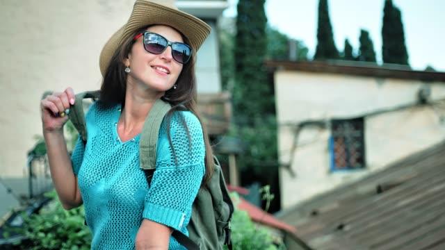 medium shot smiling pretty female hiker in hat flirting enjoying beautiful cityscape at sunset - viaggiare zaino in spalla video stock e b–roll