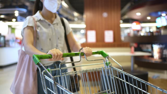 Medium shot Woman on mask with trolley cart walking in supermarket 4K Medium shot Woman on mask with trolley cart walking in supermarket market retail space stock videos & royalty-free footage